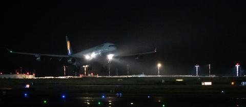 Im Dunkel der Nacht landet ein Flugzeug auf der beleuchteten Landebahn.