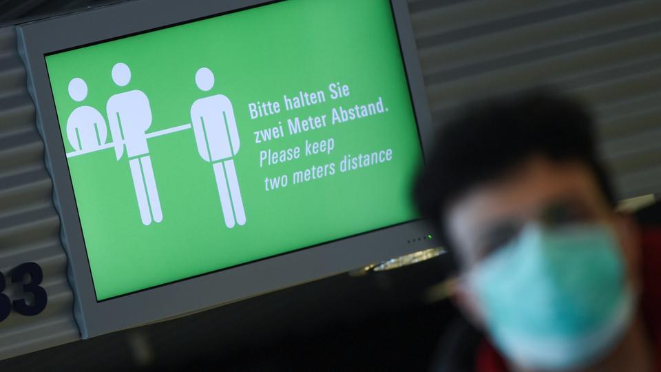"""""""Bitte halten Sie zwei Meter Abstand!"""" steht auf einem Monitor im Terminal 1 des Frankfurter Flughafens."""