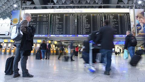 Passagiere gehen auf dem Flughafen in Frankfurt an der Anzeigetafel vorbei.