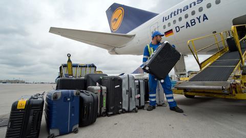 Ein Vorfeld-Mitarbeiter lädt auf dem Flughafen in Frankfurt Koffer in eine Lufthansa-Maschine.