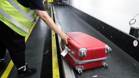 Reisegepäck von Fluggästen wird auf einem Flughafen auf die Gepäckbänder gelegt.