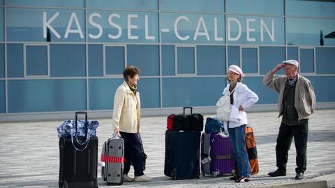 Reisende stehen vor dem Flughafen kassel-Calden