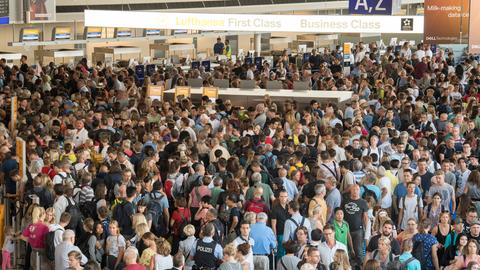 Flugreisende stehen Schlange am Frankfurter Flughafen