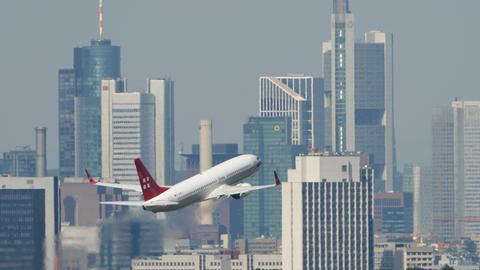 Flugzeug hebt vor Frankfurter Skyline ab.