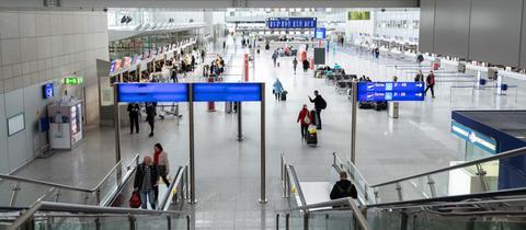 Wenige Menschen in einer Flughafenhalle