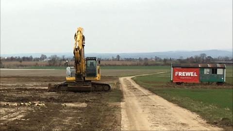 Ein Bagger und ein Protestplakat auf dem Bauland für das neue Rewe-Logistikzentrum
