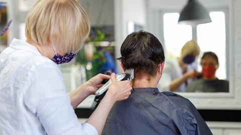 Eine Friseurin schneidet einer Kundin die Haare.