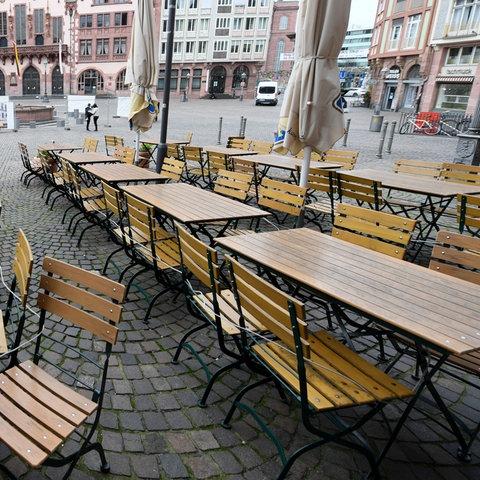 Leere Tische und Stühle einer Gaststätte stehen vor dem Frankfurter Römer.