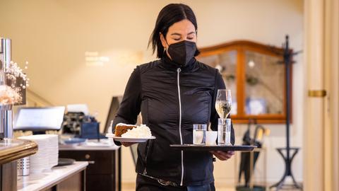 Eine Kellnerin bedient einen Gast mit Kaffee und Kuchen.