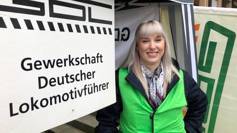 """Zugchefin Selina Kowalewsky. Neben ihr ein Schild mit der Aufschrift """"GDL-Gewerkschaft Deutscher Lokomotivführer""""."""