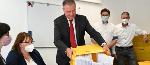 Claus Weselsky kippt eine Box mit Abstimmungszetteln auf einen Tisch.