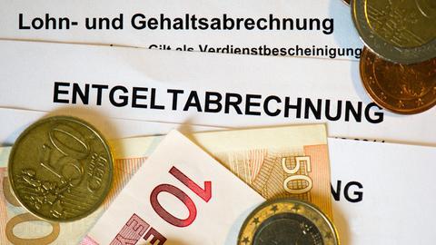 Auf Lohn- und Gehaltsabrechnungen liegen Euromünzen und Eurogeldscheine