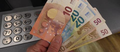 Geldscheine werden an einem Geldautomaten abgehoben