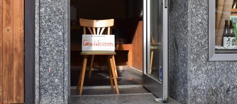 """In einer Tür steht ein Stuhl mit Schild """"Geschlossen"""""""