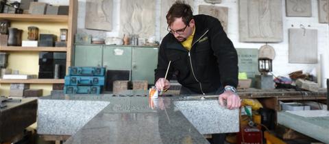 Steinmetz arbeitet an einem Grabstein