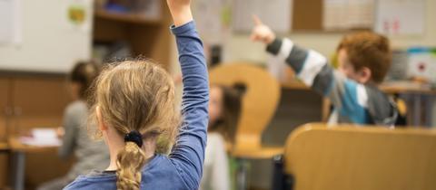 Ein Mädchen meldet sich im Unterricht in einer Grundschule in Eltville