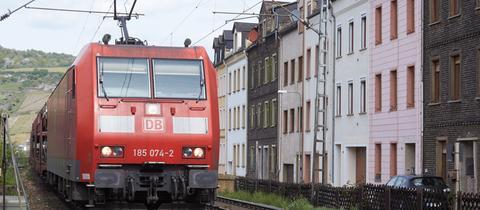 Ein Güterzug fährt bei Lorchhausen unmittelbar an Wohnhäuser vorbei