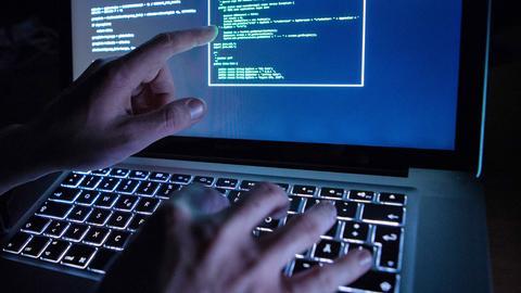 Hände tippen auf einer Laptop-Tastatur