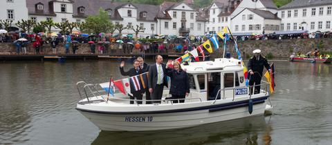 Ein Sportboot der Polizei mit Marcus Dittrich (parteilos, l), Bürgermeister von Bad Karlshafen, Marco Wanderwitz (CDU, M), Parlamentarischer Staatssekretär beim Bundesminister des Innern, und Eva Kühne-Hörmann (CDU), Justizministerin von Hessen, fahren bei der Eröffnung durch den neuen Hafen.