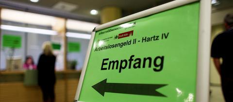 """Ein grünes Schild am Empfang eines Jobcenters mit der Aufschrift """"Empfang"""" und """"Hartz IV"""""""
