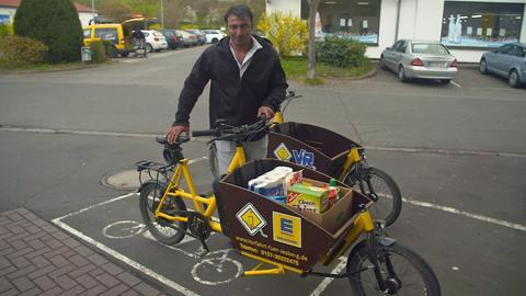 Flüchtling Zaid bringt per Lastenrad Einkäufe zu den Kunden.