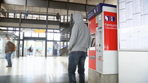 Eine Person, dunkel gekleidet mit Kapuzenpullover, steht an einem Fahrkartenautomaten der Deutschen Bahn für den Regionalverkehr. Im Hintergund ist der Bahnhof Kassel zu sehen.