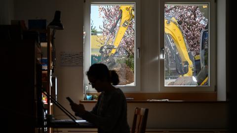 Die Silhouette einer Frau am heimischen Schreibtisch vor einem Fenster.