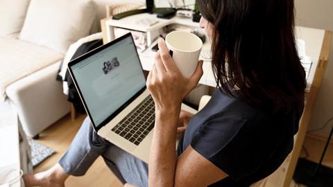 Eine Frau mit Laptop auf ihrem Schoß im Wohnzimmer
