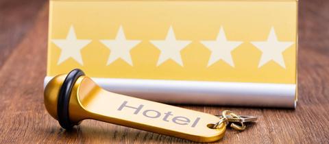 Hotelschlüssel, Schild mit Aufschrift Hotel und Sternen