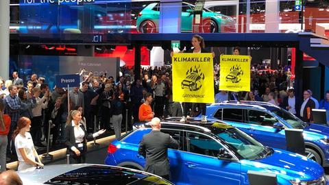 """Aktivisten von Greenpeace protestieren beim Rundgang von Kanzlerin Merkel über die IAA auf VW-Autos mit Plakaten mit Aufschrift """"Klimakiller"""""""