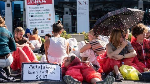 """Aktivisten von """"Sand im Getriebe"""" sitzen und liegen bei einer Blockade vor dem westlichen Eingang der IAA"""