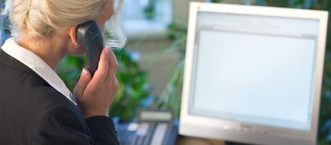 Eine Frau in Rückenansicht, die gleichzeitig telefoniert und am Computer arbeitet.