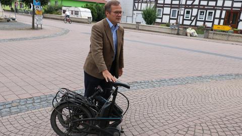 """Ein E-Bike als Klappfahrrad fährt Michael Schramek vom Verein """"Vorfahrt für Jesberg""""."""