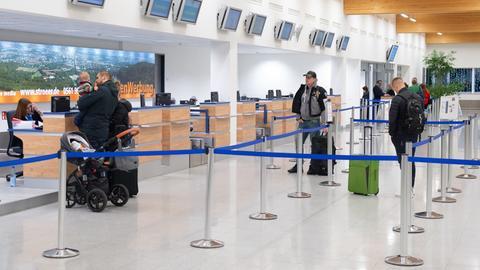 Fluggäste mit Gepäck stehen im Dezember beim Check-In im Flughafenterminal am Kassel Airport.