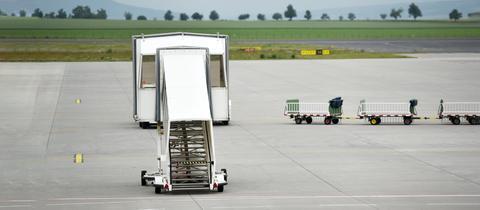 Kassel Airport - Fluggastbrücke und Gepäckwagen stehen auf dem Rollfeld