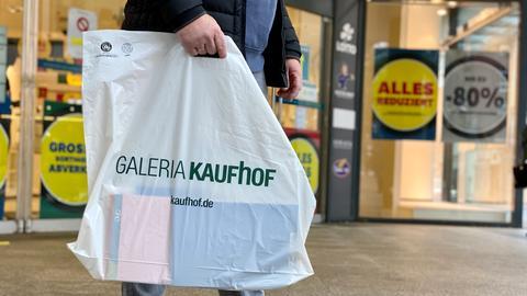 Ein Kunde trägt eine Plastiktüte von Galeria Kaufhof