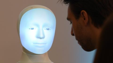 """Die Frage """"Should I kill humans ?"""" wird während einer Pressekonferenz an der TU Darmstadt hinter Roboter """"Alfie"""", einer Moral Choice Machine, auf eine Wand projiziert. I"""