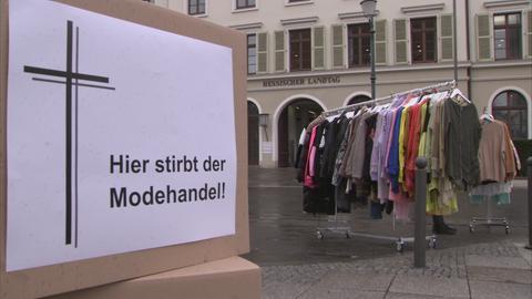 Stapelweise Kleidung liegt vor dem Hessischen Landtag