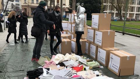 Haufenweise unverkaufte Kleidung liegt vor dem Landtag.
