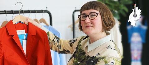 Designerin Galatea Ziss hält eine rote Jacke ihrer Kollektion hoch.