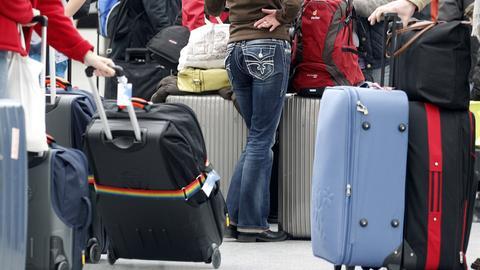 Menschen mit Koffern auf einem Flughafen.