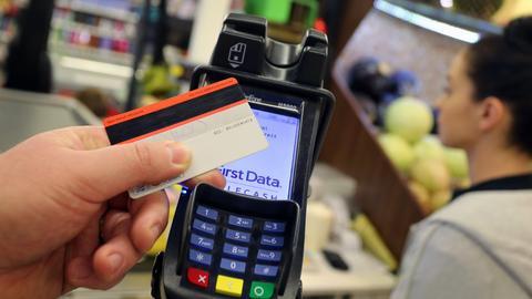 Eine EC-Karte wird an den Bezahl-Terminal an der Kasse eines Supermarktes gehalten.