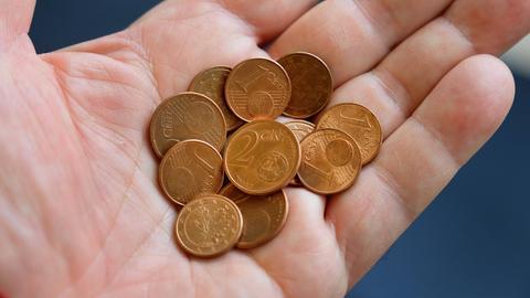 Ein Mann hält Kupfer-Cent-Münzen in der Hand.