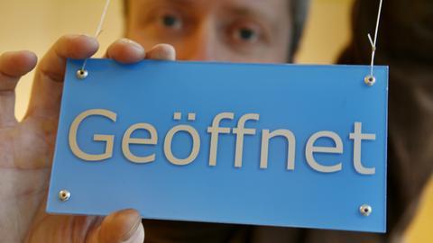 """Ein Ladenbesitzer dreht an der Tür seines Geschäftes in Wiesbaden ein Schild mit der Aufschrift """"Geöffnet"""" um."""
