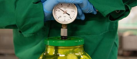 Lebensmittelkontrolleur kontrolliert Vakuum in einem Gurkenglas