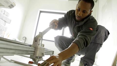 Lehrling Hassan Juma bedient auf dem Boden eine Fliesen-Schneidemaschine.