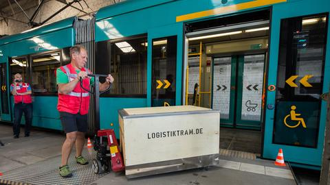 Mann beliefert Logistiktram mit Mikrodepot mit Päckchen
