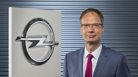Michael Lohscheller neben einem Opel-Logo.