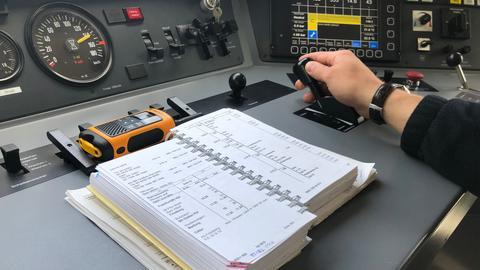 Lokführer im Führerstand mit Technik und Handbuch