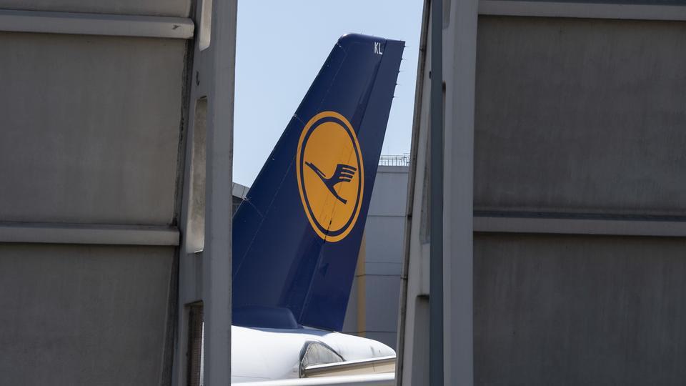 Die Heckflosse einer Passagiermaschine der Lufthansa ragt in einer Lücke in der Lärmschutzwand auf dem Flughafen Frankfurt in die Höhe.